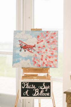 Unique wedding guestbook alternative idea - hand painted airplane painting where guests signed balloons {Elizabeth Fogarty}