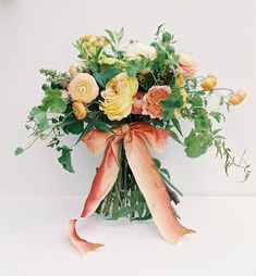 """""""Full yellow and peach garden roses and matching ranunculus and celosia mingle with scented geranium, mint, jasmine, and buds from the butterfly bush"""""""