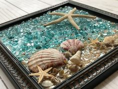 """8x8 Resin Beach Glass Window or Wall Art-Suncatcher w/ Real Seashells and Starfish for Beach House Decor/Colorful Beachy Coastal Decor  The design of crushed shell and glass, seashells and starfish is bonded (not glued) to glass with resin and framed in an 8"""" x 8"""" lightweight plastic frame, easy to Beach House Decor, Home Decor, Window Art, Beach Art, Resin Art, Suncatchers, Coastal Decor, Starfish, Sea Shells"""