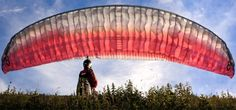 Paraglider catching the wind into his glider right before takeoff. White and red wing, gently back lighted by the sunlight, floats above his head against blue sky. Paragliding, Extreme Sports, Lifestyle Photography, Sky, Red Wing, Sunlight, Inspiration, Blue, Heaven