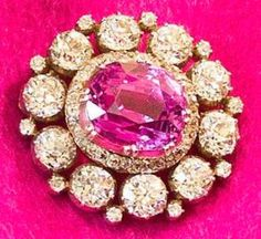 This small brooch in the Queen Elizabeth II collection includes a central pink stone framed by diamonds and surrounded by larger round diamonds. On the outer edge, small diamonds are tucked between the largest stones. Via Her Majesty's Jewel Vault.