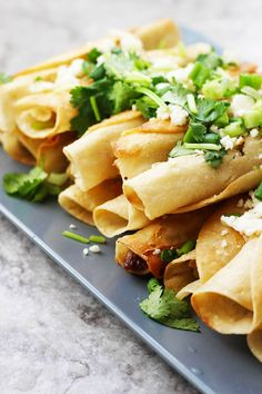 Learn how to make authentic Chicken Taquitos, also known as Flautas de Pollo.  Just five ingredients and a few garnishes makes this Mexican recipe an easy way to feed a crowd.  This easy recipe can be scaled to your needs. Chicken, salt, pepper, chile powder and tortillas, that's it! Serve these with salsa, sour cream and guacamole and you have a Mexican feast!
