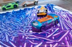 Modern Art with a Matchbox Car  Material:      Paper.      Jelly roll tray.      Kid's craft paint      Small toy cars.      Smock or bib for your tot (optional).