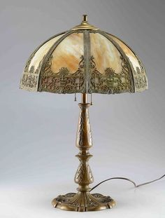 A very nice late 19th century slag glass lamp with two lights and pull chain switches. The paneled shade has a scrolled floral design to each of the eight sides with white and gold slag inserts and green slag border to the bottom. The ornate base is made of cast metal with a painted patinated brass colored finish and has an acanthus leaf design.