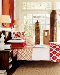 bedding..... red/white décor.... notice the 3 old wooden beams standing against the windows... and notice over the headboard there are gold/red blankets draped over a rod to create 'artwork' for the bed....