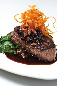 Filet mignon with a mushroom glaze, sauteed spinach, onion bacon jam, and carrot chips.