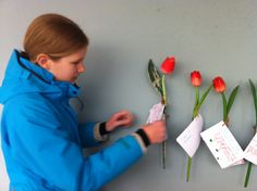 On both sides of the inner court of the Hollandsche Schouwburg (the Dutch Theatre) wooden tulips are attached to the walls. At the end of their visit the children were invited to write down their thoughts onto note cards which they tied to the tulips. This is my daughter tying her note card to a tulip. Amsterdam, the Netherlands 3/21/13. Amsterdam Tulips, Note Cards, Netherlands, Dutch, Theatre, Daughter, Walls, Invitations, Thoughts