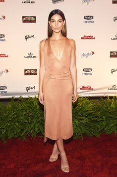 Lily Aldridge wears a belted peach-colored dress with nude Stuart Weitzman sandals