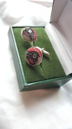 Green Woodpecker cufflinks.  Carved tagua nut, silver, sapphires.  By Andrew Birks