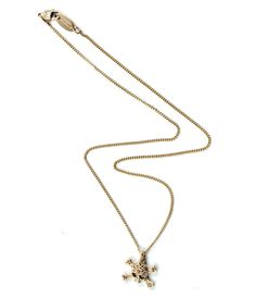 This is a classic Vivienne Westwood pendant showing the skull and crossbones encrusted with light Topaz Swarovski Crystals.