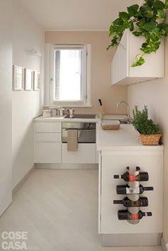 4) Cucina schermata Larga 166 cm, la zona cottura è uno spazio ricavato ex novo tra la parete del soggiorno e quella della camera da letto. È risolto con una composizione angolare che utilizza il muro della finestra con le basi e quello perpendicolare anche con pensili