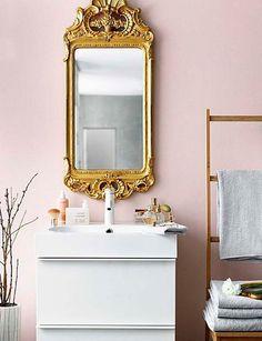 Cuarto de baño rosa con espejo dorado