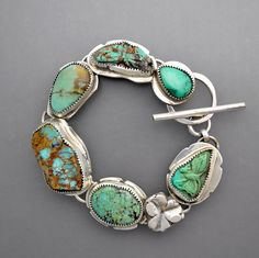 A beautiful sterling silver bracelet with a center rough turquoise, and three natural turquoise cabochons, two carved turquoise butterflies and harmonious