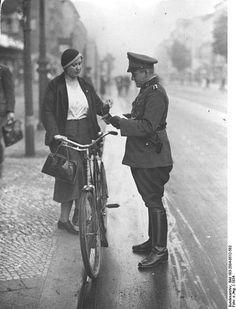 """Berlin 1934 Radfahrerin in der Chausseestrasse.Der Bildbeschreibung zufolge wurden die Personalien der """"Verkehrssuenderin"""" aufgenommen,da sie """"auf der Mitte der Fahrbahn statt aeusserst rechts gefahren ist."""