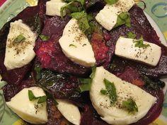 Plátky červené řepy upečené v troubě, servírované obložené mozzarellou a posypané nasekanou bazalkou.