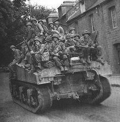 US infantry men riding Sherman tank France 1944