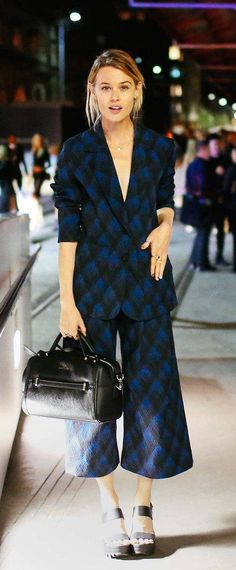 Natalie Cantell in a blue patterned culotte suit and black bag