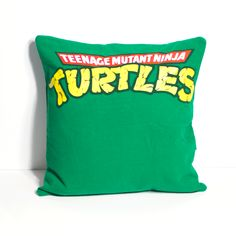 "One of a kind TMNT pillow featuring the classic logo. - As soft as your favorite tee shirt - 14"" x 14"" pillow - Envelope closure in the back for easy washing and care - Made in the U.S."