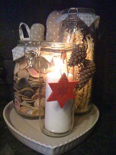 glazen bokaal kaarsje erin en decoratie met een lintje.