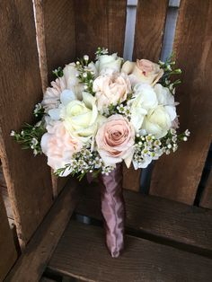 Peach carnations and blush roses make up this beautiful bridesmaid bouquet