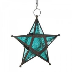 Blue Star Candle Lantern Add a candle to this five-pointed star to fill the night with celestial light! Artistic hanging lantern features ornate panels of deep ocean blue glass set into a wrought-iron