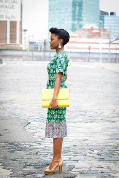 Beautiful black woman in green and blue printed dress with yellow clutch!