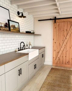 See how easy it is to update your laundry room. Focus on farmhouse touches, like a big single basin. Add in modern details, like subway tile, to keep the room fresh for years to come. A sliding barn door in a warm wood tone is the ultimate statement. Laundry Room Cabinets, Laundry Room Organization, Laundry Room Design, Laundry Rooms, Small Laundry, Laundry Room With Sink, Laundry Decor, Bathroom Laundry, Kitchen Cabinetry