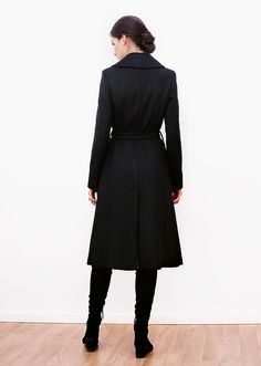 London wool coat black. Embrace a timeless design perfectly cut in black, pure Italian wool. Displaying a flattering, flared silhouette, the coat is finished with a matching tie belt. It has a deep slit at the back and side pockets.