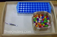 Fine Motor Skills - Tweezers, small pom-poms, small form ice cube tray. Child uses tweezers to pick-up individual pom-poms and then drop into individual cube form.