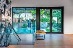 Full windows frame a verdant backyard.