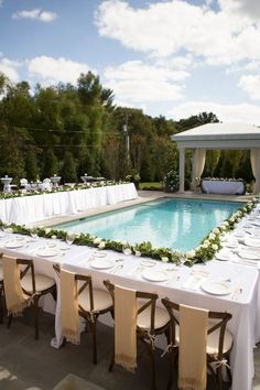 poolside reception table decorated with a greenery and white rose table garland