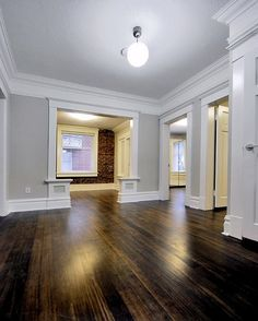 The best warm gray paint colour shown in Open layout with dark wood flooring and brick feature wall. Photo via Chris Nelson Inc floors grey walls The 4 Best Warm Gray Paint Colours: Sherwin Williams House Design, House, Grey Walls, House Styles, White Baseboards, New Homes, Dark Wood Floors, Warm Grey Paint Colors, Brick Feature Wall