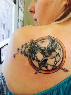 Hunger Games tattoo with mockingjay and dandelion