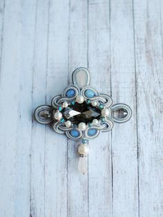 Soutache handmade embroidery brooch in grey blue and whte colors with crystals. This exquisite brooch incredible shine on your jacket or dress. Complete image of small earrings and you can not look away!  FREE SHIPPING  Brooch made in technology soutache with crystals, glass pearls, Japan metalic beads. The back side is sewn felt.  Lenght - 8.5 cm (3,34 inch) Width - 7.5 cm (2,75 inch) Height - 1 cm (0.39 inch) Weight - 16 g (0,56 oz)  Brooch can be made to order in any color and size…
