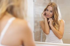 A woman is looking in the mirror, touching her cheeks.