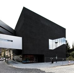 Bergbau-Museum Anbau | DBM - The closed portion of the facade consists of a seamless rough plaster surface in black color with blown glittering silicon carbide chips. This is made possible by a curtain-ventilated facade plaster with bearing plates expanded glass granulate and the appropriate reinforcement. The roof is formed by color conformed to the plaster facade elevated concrete blocks.