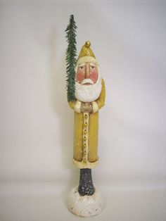 This slim guy stands 13 1/4 inches high and is made from a paper mache/sawdust mixture. He has been painted, stained, sealed and dusted with lots of snowy glitter.    He wears golden bell buttons and a golden bell pompom and carries a Canadian pine sprig.    ....a neat addition to your Santa collection.    I do ship worldwide. Please message me for rate.    Thanks for looking:)