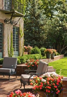 The front yard is organized by soft lawn spaces and large Birch trees. The entrance to the home is accentuated by masses of annual flowers that frame the bluestone steps.