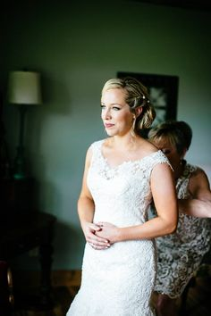 Beautiful Bride waits while her Mother finishes buttoning up her gown / Lace wedding dress / LEB is weekend wedding destination & barn event venue located in the Texas Hill Country / Photo: J. Violet Photography