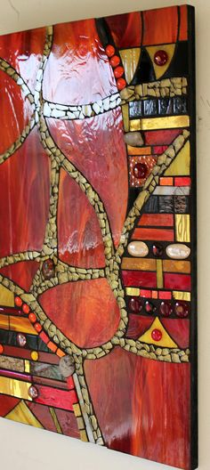 This striking, abstract, glass mosaic features beautiful red glass with streaks of a quiet orange. It is titled Paths in Life. The gold glass in the paths is tempered glass from a recycled car windshield. A wide variety of materials was used in its creation including mirror glass,
