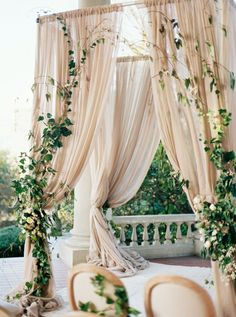 Neutral-hued chuppah festooned with fresh greenery
