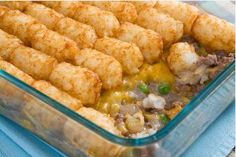 Cowboy Casserole.  1 pound hamburger  1 medium onion, chopped  1 can  cream of mushroom soup  1  package frozen peas  garlic powder, to taste  pepper, to taste  1 1/2 cups Cheddar cheese  1 pound bag tater tots