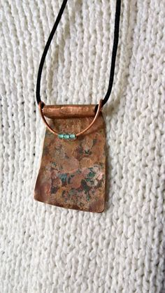 This OAAK rustic, hammered copper asymmetrical pendant with aqua beads is a great fashion accessory. Upcycled from copper sheet and reclaimed electrical wire. Glass aqua beads are a great complement to the blue green patina found on the copper. Pendant is assymetrical and beads