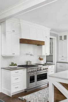 Cottage style range hood features a wood trim above a swing arm pot filler mounted on white arabesque backsplash tiles completing a cooktop design. Kitchen Hood Design, Kitchen Vent Hood, Kitchen Stove, Kitchen Redo, Home Decor Kitchen, New Kitchen, Home Kitchens, Kitchen Remodel, Kitchen Cabinets