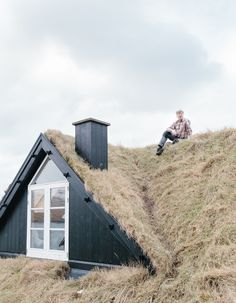 Sigurd Nordendal sits on the roof of his home