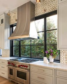 Remodeling Kitchen Lighting A stainless steel French kitchen hood, illuminated by Boston Functional Library Wall Lights, stand in front of windows and over a Wolf dual range. Kitchen Hoods, Kitchen Stove, New Kitchen, Kitchen Backsplash, Gold Kitchen, Kitchen White, Backsplash Ideas, Kitchen Utensils, Kitchen Cabinets