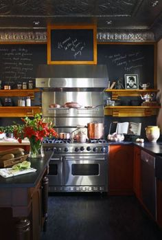 This is fun and different: orange lowers, honed slate countertop, copper ceiling, chalkboard and a beyond gorgeous stove.