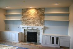 Fireplace makeover...using the whole wall, move the old kitchen cabinets down there for storage.