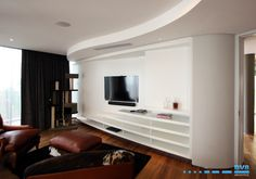 Wall unit with peeled shelves and sliding doors to hide the TV unit. Duco sprayed white with walnut inlays. Curved ceiling bulkhead.