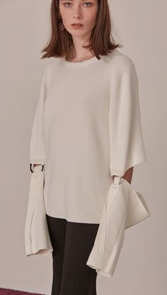 Wide neck top with elbow cutaways and dolman sleeve. Sliver-toned ring hardware above sleeve for adjustments. Designed to be a relaxed cut.